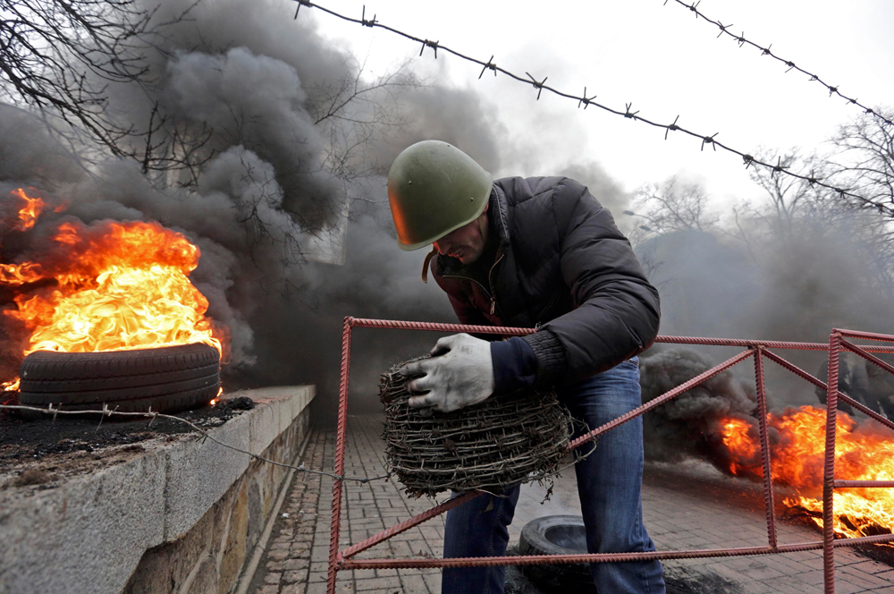 An anti-government protester reels barbed wire around a barricade during clashes with riot police in the Independence Square in Kiev