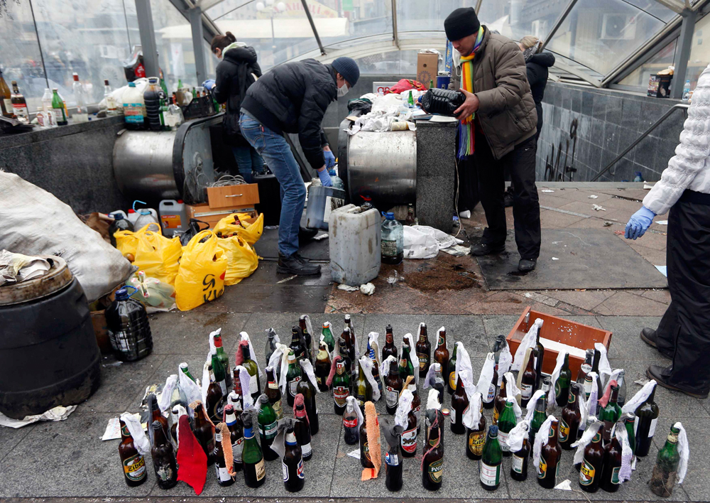 Anti-government protesters prepare Molotov cocktails during clashes with riot police in the Independence Square in Kiev
